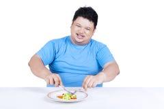 Prova dell'uomo da essere a dieta mangiando insalata Fotografia Stock