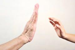 Prova della mano del ` s del bambino per toccare mano senior o la mano della donna anziana Selecti Immagini Stock