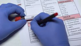 Prova di ANA, medico che controlla le malattie nello spazio in bianco del laboratorio, mostrante campione di sangue in tubo archivi video