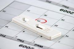 Prova di gravidanza e una data circondata - alto vicino Immagini Stock