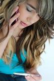 Prova e telefono di gravidanza teenager della holding della ragazza Fotografia Stock