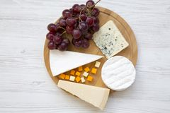 Provando vários tipos de queijo com uvas em uma placa de madeira redonda Alimento para o vinho, vista superior Configuração lisa Fotografia de Stock Royalty Free
