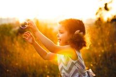 Prove del bambino per prendere una bolla al sole Priorità bassa di Bokeh Immagini Stock Libere da Diritti