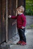 Prove del ragazzino per aprire vecchia porta Immagini Stock Libere da Diritti