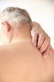 Prove dell'anziano per graffiare la sua parte posteriore nuda Immagine Stock