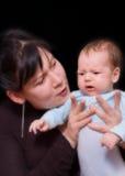 Prove della madre per calmare il suo bambino gridante Immagine Stock