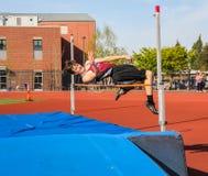 Prove maschii dell'atleta della High School per rimuovere barra nel salto in alto nel raduno di pista Immagine Stock Libera da Diritti
