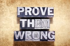Prove them wrong. Phrase made from metallic letterpress type on grunge cardboard background Stock Photography