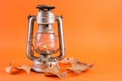 Provea de gas la linterna con la luz ardiente y las hojas secas caidas Imagenes de archivo