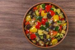 Provencal maträttratatouille i en kruka som göras av keramik på tabellen som göras av ekplankor medf8ort Riktig näring och bantar arkivfoton