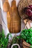 Provence-Artkücheninnenraum, weiße hölzerne Wand, Schneidebrett, Geräte, Rattanküstenmotorschiff, Leinentuch, neues Gartenkräuter Stockfotografie
