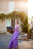 Flicka med en korg av nytt klippt lavendel i den gammala staden Arkivbild