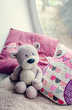 Provence style interior. Warm and cozy window seat with Teddy Bear and cushions. Light home decoration in pink and purple tones. Retro living room Royalty Free Stock Photo
