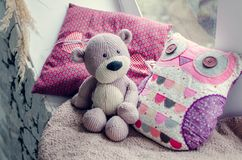 Provence style interior. Warm and cozy window seat with Teddy Bear and cushions. Light home decoration in pink and purple tones. Retro living room Royalty Free Stock Photography