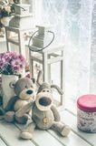 Provence style interior. Warm and cozy window seat with Teddy Bears and flowers. Light home decoration in pink and purple tones. Retro living room Stock Image