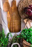 Provence style kitchen interior, white wooden wall, cutting board, utensils, rattan coaster, linen towel, fresh garden herbs rosem Stock Photography