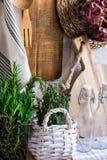 Provence style kitchen interior, white wooden wall, cutting board, utensils, rattan coaster, linen towel, fresh garden herbs Royalty Free Stock Photo