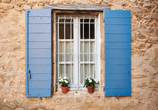 Provence window. White Provence window with blue covers and pots of flowers in Grambois village, South France Royalty Free Stock Photos