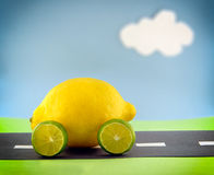 The Proverbial Lemon. A lemon car with lime wheels driving along a construction paper scene stock photo