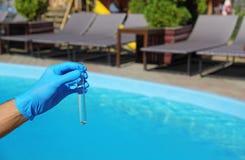 Provetta della tenuta dell'uomo con acqua contro la piscina fotografie stock libere da diritti
