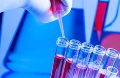 Provette con la pipetta su liquido rosso in laboratorio Immagini Stock