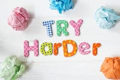 Provi il consiglio motivazionale più duro con le varie lettere colorate sulla tavola o sul fondo di legno bianca fotografie stock