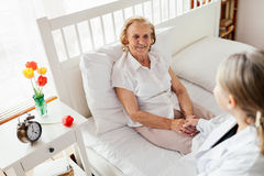 Providing care for elderly. Doctor visiting elderly patient at home. Royalty Free Stock Photos