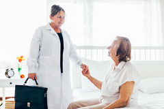 Providing care for elderly. Doctor visiting elderly patient at home. Stock Image