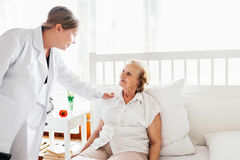 Providing care for elderly. Doctor visiting elderly patient at home. Stock Photos