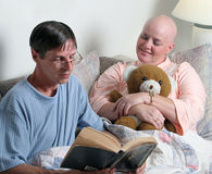 Providing Comfort 2. A man volunteering to read the bible to a cancer patient. (focus is on the woman's face royalty free stock photography