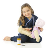 Providing Pills for Sick Dolly. An adorable elementarynurse in scrubs preparing to give her doll some pills. On a white background stock photography