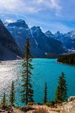Province of Alberta, Canadian Rockies. The cold northern sun is reflected in the icy water of the lake Moraine. The concept of stock photography