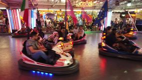 Bumper Cars arena. Province of Bologna, Italy - June 8, 2019: Children and young people playing driving wild bumper cars, in the Amusement Park night arena and stock footage