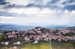 Province of Fermo, Italy. Village on a hill. Rural panorama of Italian countryside. Province of Fermo, Italy. Village on a hill under dramatic cloudy sky Royalty Free Stock Photo