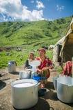 PROVINCIA di NARYN, KIRGHIZISTAN - 20 luglio 2016 giovane ragazzo e madre che producono burro dal latte Fotografia Stock Libera da Diritti