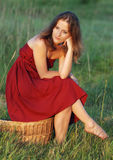 Provincial girl. A beautiful girl in red clothes sits on a large basket in the field Royalty Free Stock Photos