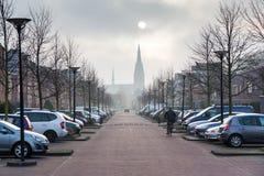 Provinsiella Holland Cityscape med sol- förmörkelse, gatan av den lilla Flanders staden med den gotiska kyrkan, två rader av bila Arkivbild