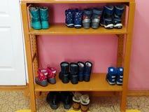 Provinzieller Kindergarten Die Stiefel der Kinder sind auf einem selbst gemachten Holzregal lizenzfreies stockbild