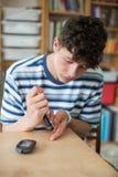 Provningsblod Sugar Level At Home för tonårs- pojke arkivbild