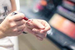 Provningsläppstift färgar på en hand i ett kosmetiskt lager royaltyfria foton