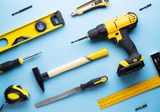 Provocação criativa: uma disposição lisa de ferramentas amarelas da mão em um fundo azul fotografia de stock