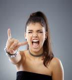 Provocative girl. Shouting eyes closed, showing rock on hand gesture Stock Image