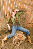 Provocative position young cowgirl on hay Royalty Free Stock Photos