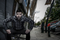 Provocative self-confident man sitting at the street in ready to stand up and fight pose Royalty Free Stock Images