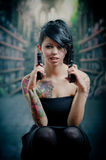 Provocative tattooed girl holding gun Royalty Free Stock Photography