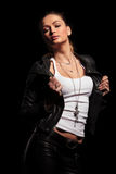 Provocative young woman is pulling her leather jacket's collar Stock Images