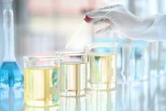 Provrör med flytande i laboratorium-, doktorshandinnehavdroppglass med stekflott eller den genomskinliga exponeringsglaspipetten, fotografering för bildbyråer