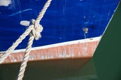 Prow of boat tied up in water with knotted rope Royalty Free Stock Photo