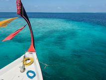 Prow of colorful dhoni boat with prayer scarves floating over coral reef. Prow of colorful dhoni boat with prayer scarves and roses floating over coral reef Stock Images