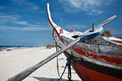 Prow of colorful old beached Portguese fishing boat with oar Royalty Free Stock Photography